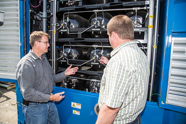 Ruslan Kosyan, Hydrogenics Project Engineer (right), shows Joe Pratt, Sandia Project Manager (left), the hydrogen storage system within the fuel cell unit.