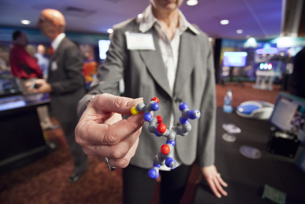 By combining innovative science, research, and development across the system of national laboratories, researchers are able to better understand (and confront) global biological threats. In this photo, Paula Imbro (a representative of Sandia National Laboratories) holds a molecular model that is specifically designed to combat the biotin, Botulinum. This exhibit featured a number of technologies, some of which are commercially licensed for the detection and diagnosis of exposure to biotoxins. The molecule pictured was identified by researchers from Brookhaven National Laboratory. (Photo by Sarah Gerrity, DOE)