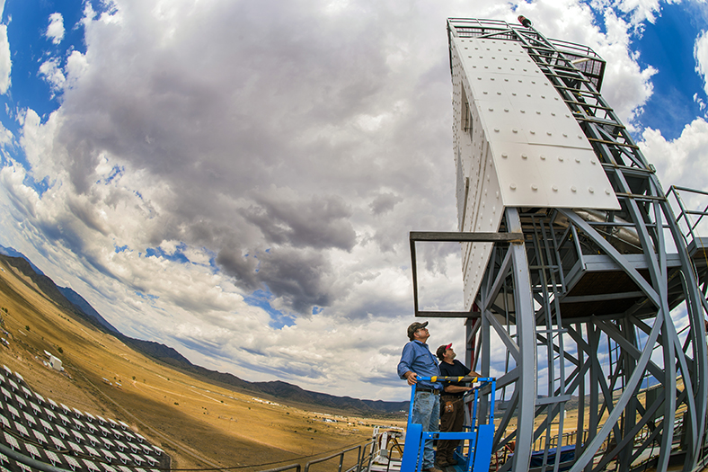 Technologists John Kelton and Daniel Ray (both in Sandia's Concentrating Solar Technologies Dept.) perform inspection of the falling-particle receiver during a cloud delay atop the NSTTF's Solar Tower at Sandia. (Photo by Randy Montoya)