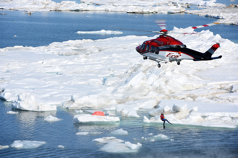 A helicopter lowers a swimmer into the Arctic Ocean during a search-and-rescue exercise near Oliktok Pt. The exercise, which involved UASs and multiple participants, took place in the Warning Area under Sandia's stewardship. (Photo by Coast Guard Petty Officer 2nd Class Grant DeVuyst)
