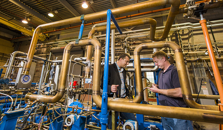 Jim Pasch, principal investigator of the sCO2/Brayton-cycle R&D program, and Darryn Fleming, principal investigator of the sCO2/Brayton-cycle heat-exchanger program, investigate a turbine and compressor inside a test facility at Sandia. (Photo by Randy Montoya)