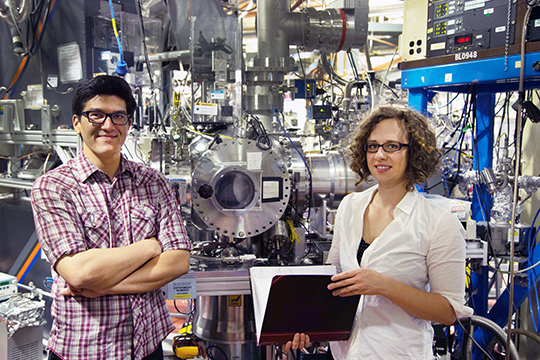 Sandia chemist John Savee (left) identified cycloheptadiene as the best fuel for creating a detectable QOOH, and Sandia computational expert Ewa Papajak (right) and her adviser, Judit Zádor, used quantum chemistry to explain the mechanism of the reaction. Savee and Papajak appear in front of an instrument, the Multiplexed Photoionization Mass Spectrometer in the Advanced Light Source at Lawrence Berkeley National Laboratory, that took direct measurements. (Photo by David Osborn)