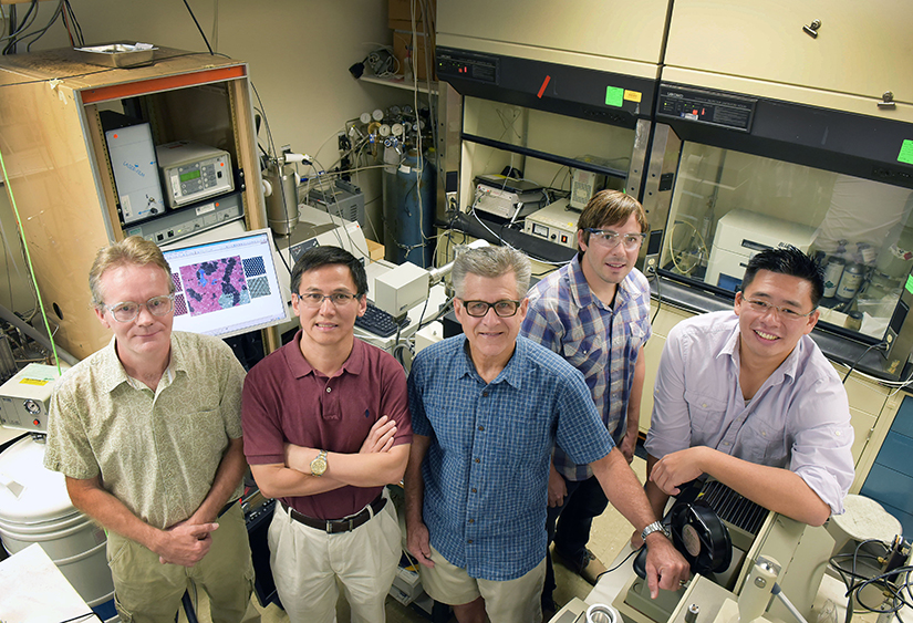 Sandia/UNM Advanced Materials Laboratory researchers, from right, Stan Chou, Bryan Kaehr, Jeff Brinker, Ping Lu, and Eric Coker, gather in a lab where work on the catalyst molybdenum disulfide was achieved. (Photo by Randy Montoya)