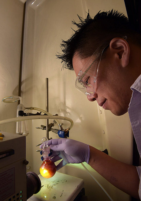 Sandia post-doctoral fellow Stan Chou demonstrates the reaction of more efficiently catalyzing hydrogen. In this simulation, the color is from dye excited by light and generating electrons for the catalyst molybdenum disulfide to evolve hydrogen. (Photo by Randy Montoya)