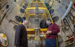 Efrain O'Neill, left, an electrical engineering professor at the University of Puerto Rico, Mayagüez, who is spending a year working at Sandia, talks energy research with senior manager Tito Bonano. (Photo by Randy Montoya)