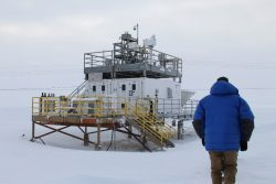 Photo of researcher walking up to snow-covered ARM climate research facility.