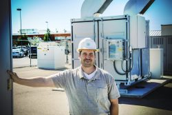 Photo of engineer next to electrical energy storage systems.