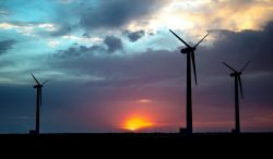 Photo of three wind turbines in front of a sunset.