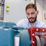 A researcher examines Sandia's new wind turbine motor, which will allow the distributed energy team to study how real wind farms will behave under a variety of conditions and in different locations.