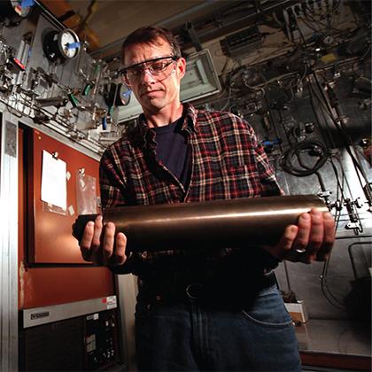 Sandia researcher Brian Somerday prepares to load a hydrogen pressure vessel into a laboratory furnace.