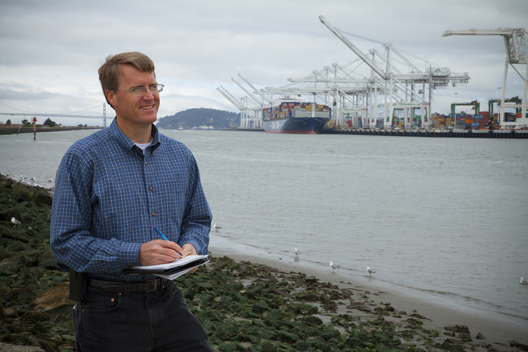 Sandia researcher Joe Pratt stands near the Port of Oakland, one of the west coast ports he studied to learn whether hydrogen fuel cells are a viable power source for docked ships. (Photo by Steffan Schulz)