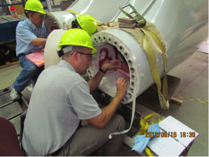 Sandia staff installing Fiber Bragg Grating sensors in the roots of 13 m wind-turbine blades used at the Scaled Wind Farm Technology (SWiFT) facility.