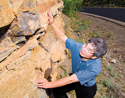 Yifeng Wang examines a sedimentary outcrop in New Mexico's Tijeras Canyon. Wang is the lead author of a paper in Nature Communications that offered insights into pore size and distribution in horizontal slices of sedimentary rock. (Photo by Randy Montoya)